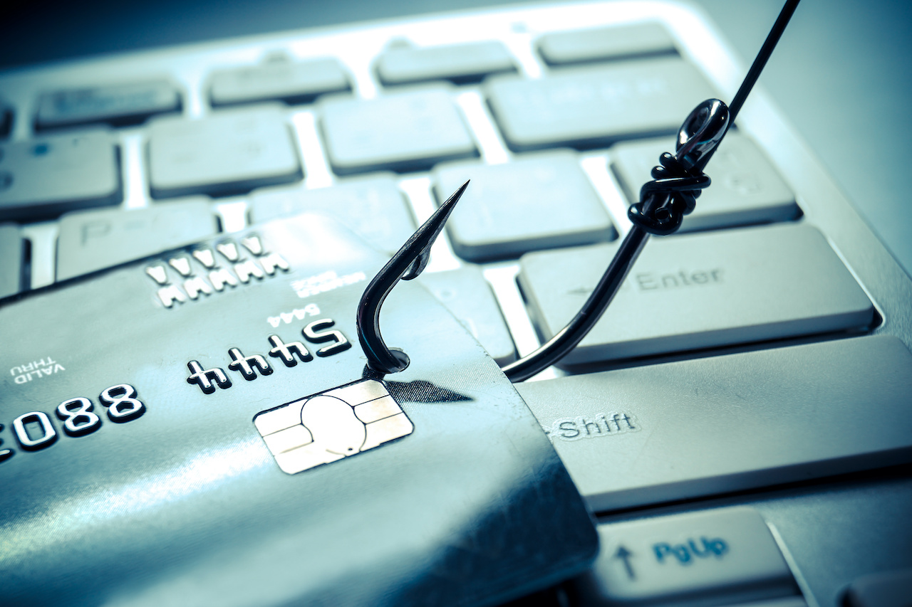 a hook stabs through a credit card on top of a keyboard, symbolizing a phishing attack
